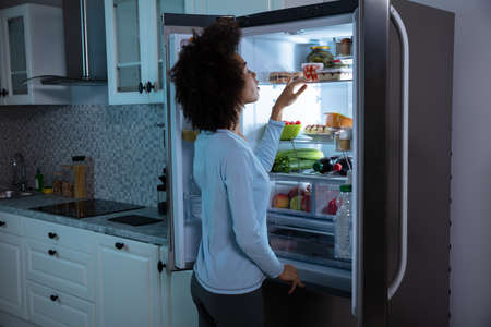 Side View Of Young African Woman Searching Food In An Open Refrigerator