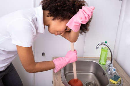 Tired Person Wearing Pink Gloves Cleaning Sink Filled With Water With Cup Plunger
