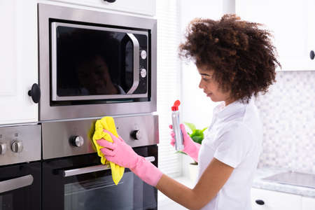 Close-up Of A Smiling Female Janitor Cleaning Oven With Yellow Napkin In The Kitchen Stock Photo