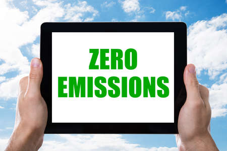 Mans Hand Holding Digital Tablet With Zero Emissions Text On Screen Against Cloudy Sky