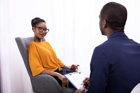 Young African Woman Sitting Near Psychologist With Clipboard To Treat Depression