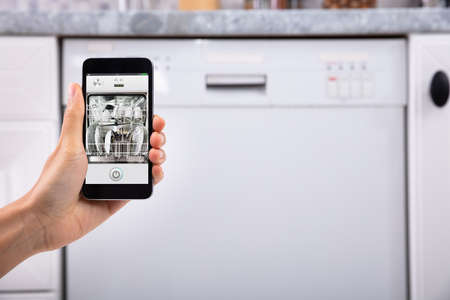 Close-up Of A Womans Hand Operating Dishwasher With Mobile Phone