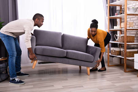 Side View Of A Smiling Young African Couple Lifting Sofa In Living Room