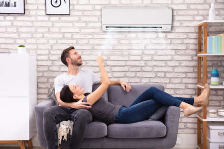 Happy Young Couple Sitting On Sofa Operating Air Conditioner At Home Banco de Imagens