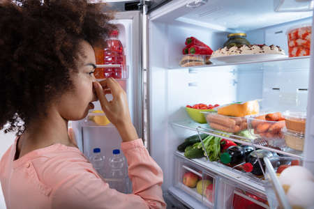 Side View Of Young Woman Recognizing Bad Smell Coming From The Refrigerator Covering Her Nose