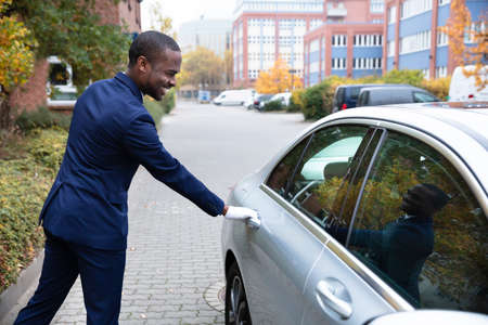 Side View Of Smiling Young African Male Valet Opening Car Door