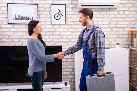 Side View Of Male Technician Shaking Hands With Happy Woman At Home
