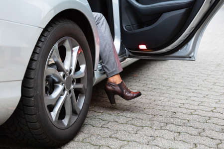 Close-up Of A Womans Feet With High Heels Getting Out From Car