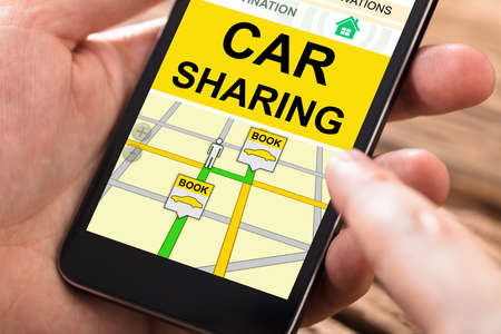 Close-up Of A Persons Hand Using Car Sharing Application On Mobile Phone
