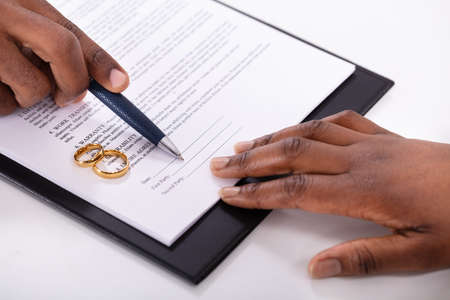 Judge Assisting Client In Filling Contract Form With Pair Of Golden Rings