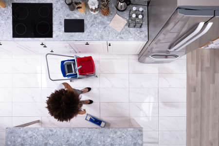 Female Janitor Cleaning The White Floor With Mop In Modern Kitchen Stock Photo