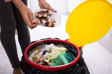 Close-up Of A Woman's Hand Throwing Cake In Trash Bin