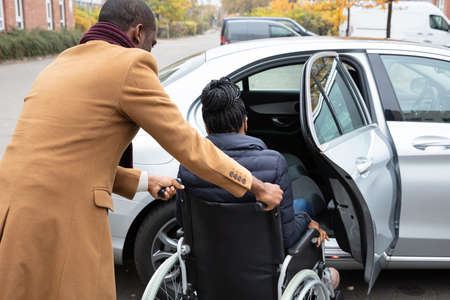 Man With Her Wife Woman Sitting On Wheelchair Moving Towards Car