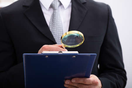 Close-up Of  Businessman Analyzing Document  Through Magnifying Glass At Workplace Stock Photo