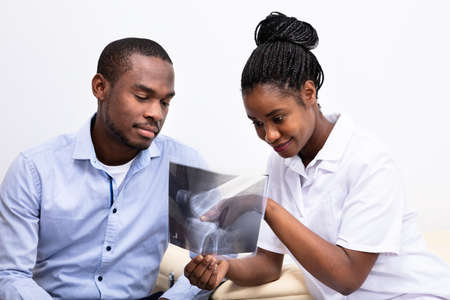 Young Female Doctor Showing Knee X-ray To Male Patient