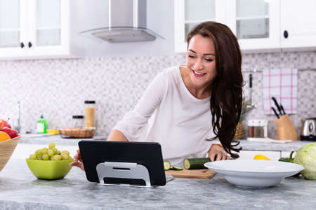 Happy Young Woman Using Digital Tablet While Cooking Food In Kitchen