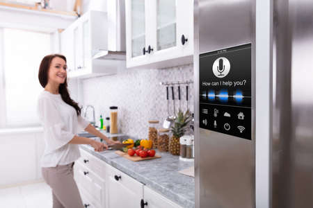 An Oven With Voice Recognition Function Near Smiling Young Woman Cutting Vegetables In Kitchen
