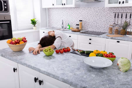 Tired Woman Sleeping On Kitchen Counter Near Fresh Fruits And Vegetables