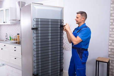 Male Serviceman In Overall Working On Fridge With Screwdriver In Kitchen Stock Photo