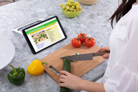 Woman Cutting Cucumber With Kitchen Knife Near Cooking Recipes On Digital Tablet Screen
