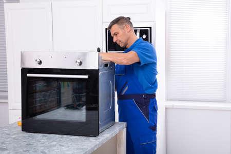 Mature Male Technician Repairing Oven On Kitchen Worktop