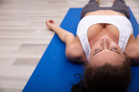 Athletic Young Woman Lying On Blue Yoga Mat Stock Photo