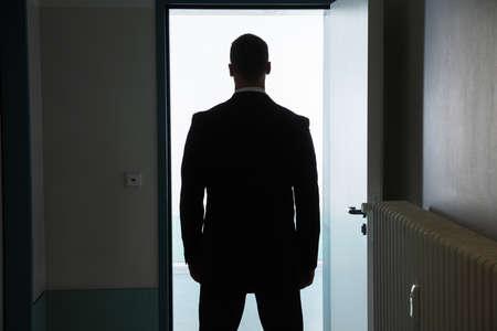 Rear View Of A Businessman Standing In Front Of Open Door