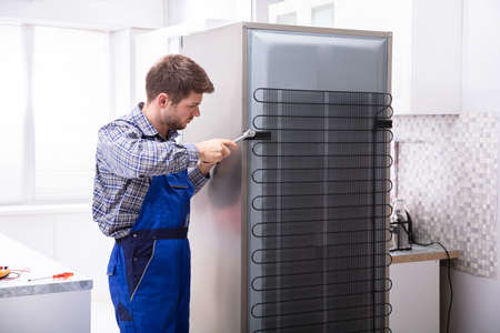 Serviceman In Overall Working On Fridge With Wrench In Kitchen