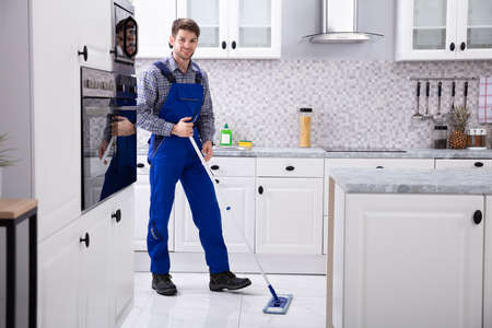Smiling Male Janitor Cleaning Floor With Mop In Kitchen