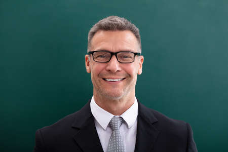 Happy Businessman In Spectacles Against Green Background Stock Photo