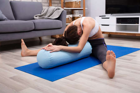 Young Woman Practicing Yoga On Bolster At Home Standard-Bild