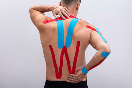 Shirtless Man With Physio Tape Applied On His Body. Body shape was altered during retouching Stock Photo