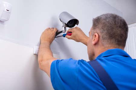 Nahaufnahme eines männlichen Technikers, der die Cctv-Kamera an der Wand mit einem Schraubendreher einstellt