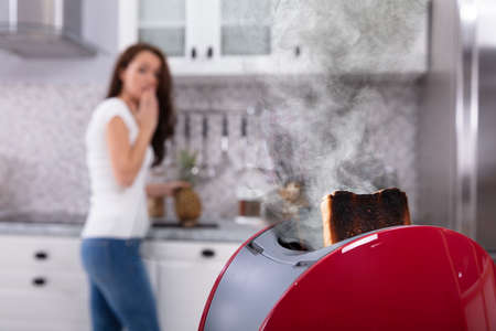 Close-up Of A Red Toaster With Burnt Toast While Woman Working In Kitchen Stock Photo