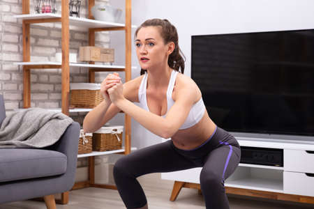 Happy Woman Doing Squat Exercise On Fitness Mat At Home