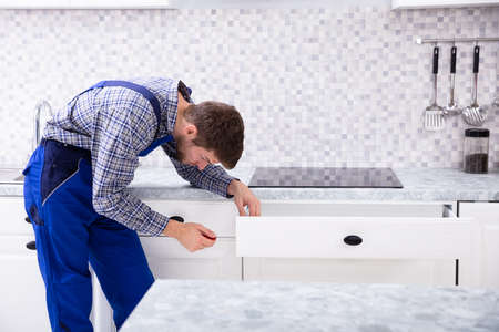 Close-up Of A Male Carpenter Installing Door Of Drawer In The Kitchen Stock Photo