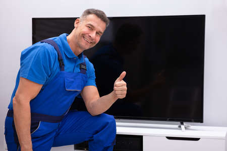 Smiling  Mature Technician Showing Thumb Up In Front Of Television Stock Photo