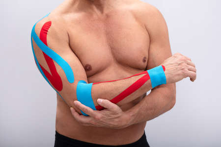 Mid-section  Man With Physio Tape On His Hand Against White Background. Body shape was altered during retouching