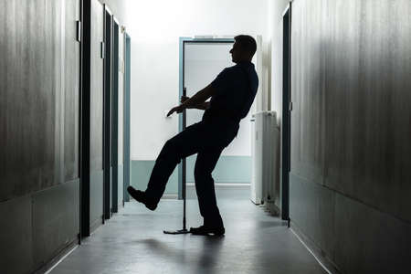 Silhouette Of A Mature Man Falling While Mopping Floor In The Corridor Stock Photo