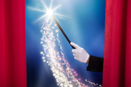 Close-up Of Magician's Hand Holding Magic Wand Behind Red Stage Curtain