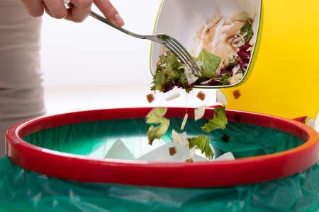 Primo piano della mano di una donna che getta le verdure nel cestino