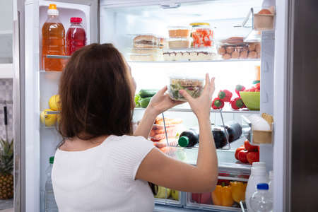 Rear View Of A Young Woman Taking Food From Refrigerator Фото со стока