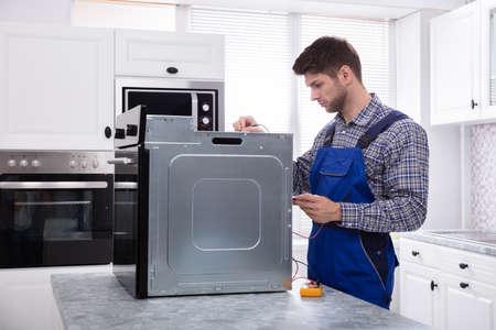 Macho joven reparador de horno de reparación con multímetro digital en la cocina Foto de archivo