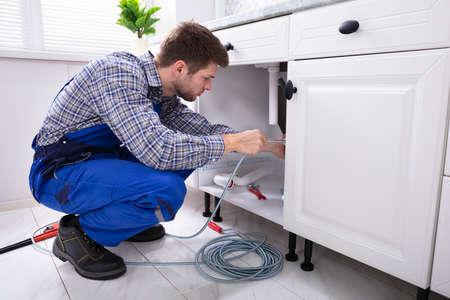 Jeune homme plombier nettoyage tuyau d'évier bouché dans la cuisine Banque d'images