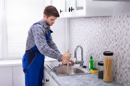Side View Of A Male Plumber Using Plunger In Kitchen Sink