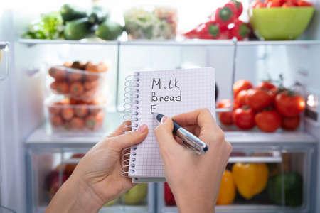 Hand, die Liste der Lebensmittel auf Spiralnotizblock vor einem offenen Kühlschrank macht