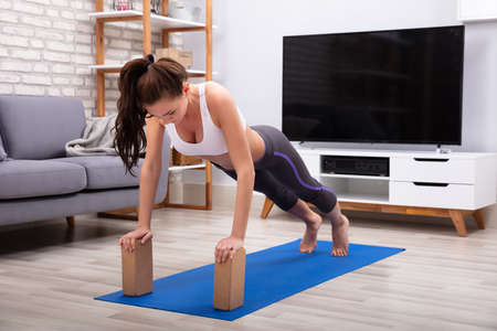 Fit Young Woman Using Wooden Blocks While Doing Exercise On Yoga Mat