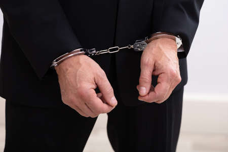 Photo of criminal businessman arrested wearing handcuffs Banco de Imagens