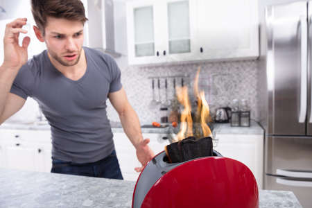 Portrait Of Scary Man Looking At Slice Of Burn Coming Out Of Toaster