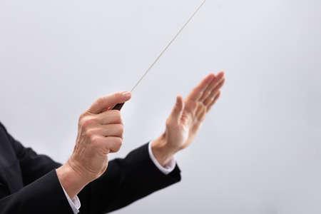 Close-up Of A Person's Hand Directing With Conductors Baton Archivio Fotografico
